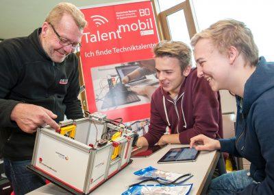 Thomas Boutter und Antonio Becker von der Initiative Talentmobil machen mit den Schülern der A1EM Experimente an Modellen zur Gebäudesystemtechnik.